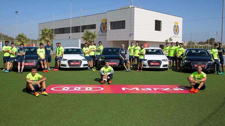 Yellows players and staff pose with the Audi cars.