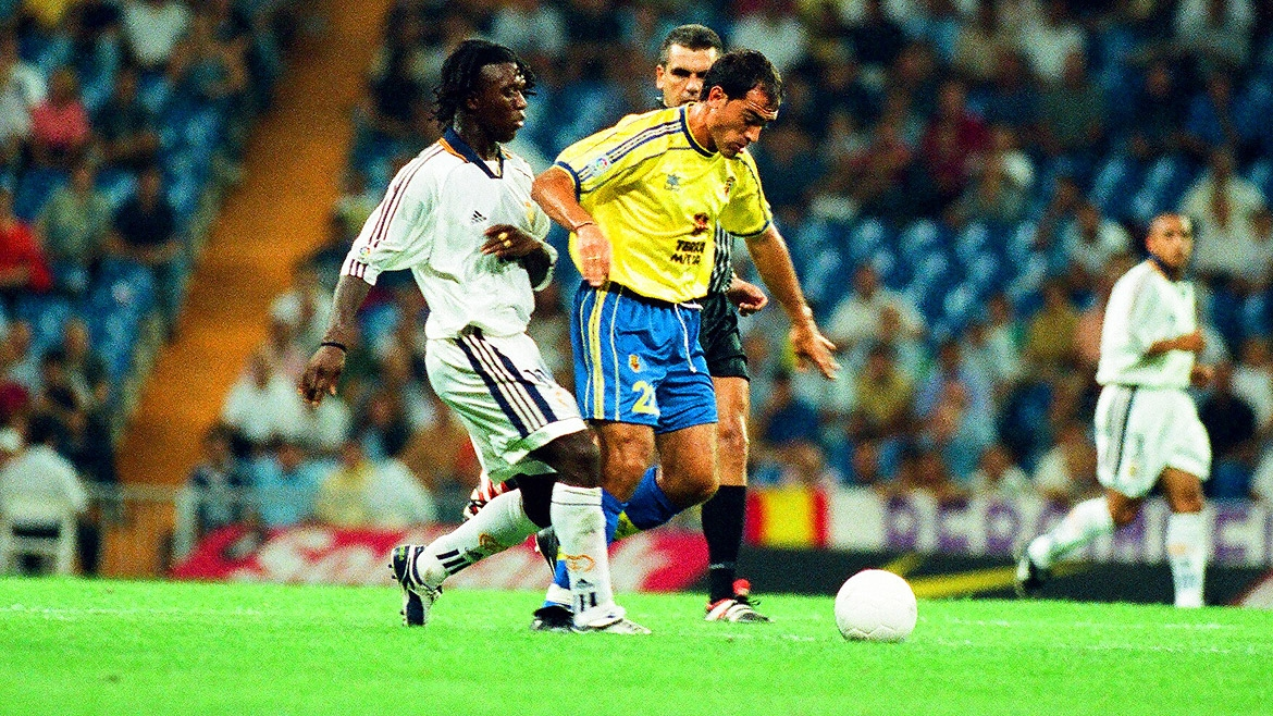 Centre midfielder Alberto Saavedra holds off Real Madrid's Clarence Seedorf.